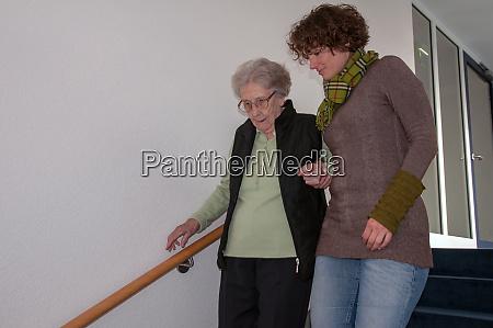 betreuer hilft seniorin beim treppensteigen