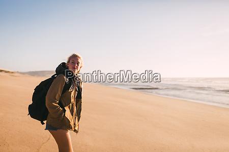 frau traegt rucksack am strand
