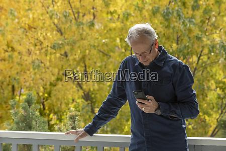 mann mit telefon von herbstbaeumen