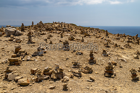 many stacked stones on a hill