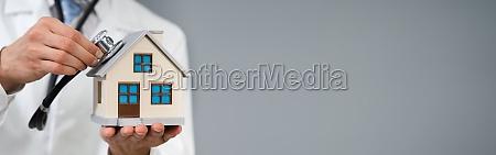 mann mit stethoskop um modellhaus zu