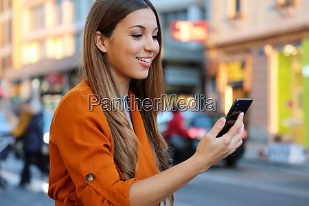 happy beautiful young woman using smart