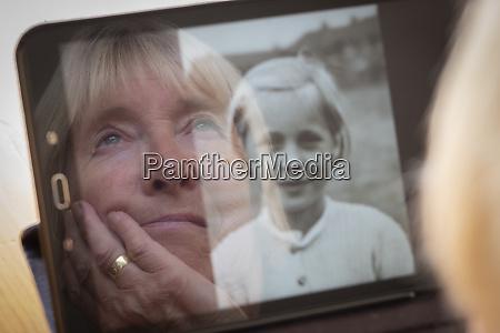 senior kaukasische frau blickauf alte fotos