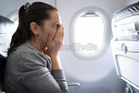 frau mit angst angriff in flugzeug