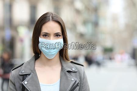 frau mit schutzmaske mit blick auf