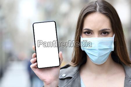 frau mit schutzmaske zeigt handy bildschirm