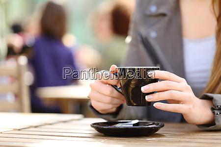 frau haelt kaffeetasse auf ihren haenden