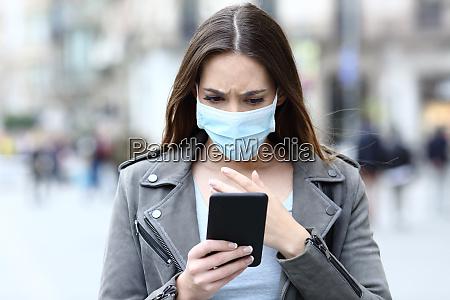 erschrockenes maedchen mit maske lesen nachrichten