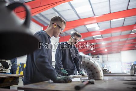 lehrlingsingenieure inspizieren rohrbiege in der metallfabrik