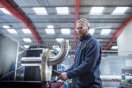 ingenieur betrieb roboter armschweissmaschine in metallfabrik