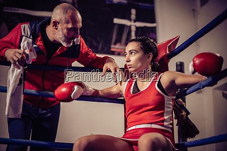 boxtrainer im gespraech mit boxerin sitzen
