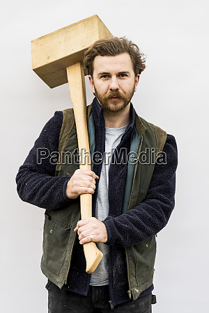 portrait of bearded man holding wooden