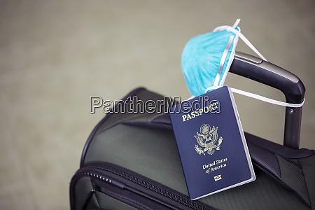 persoenliches gepaeck mit reisepass und grippevirusmaske