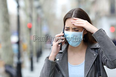 besorgte frau mit schutzmaske telefoniert auf