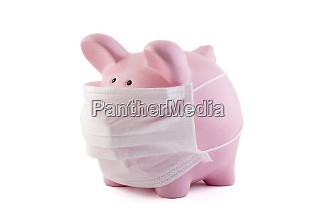 rosa sparschwein mit schuetzenmedizin maske isoliert