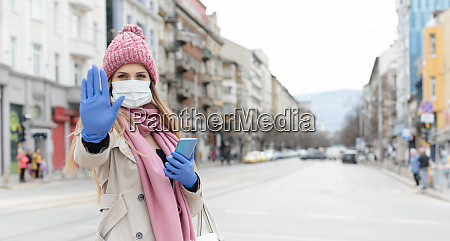 frau traegt corona maske gibt stoppschild