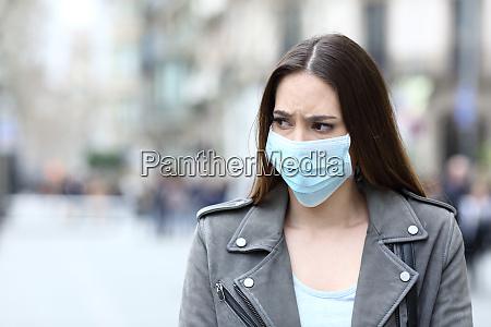 veraengstigte frau mit schutzmaske vermeidet ansteckung
