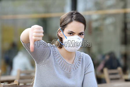 woman doing thumbs down wearing mask