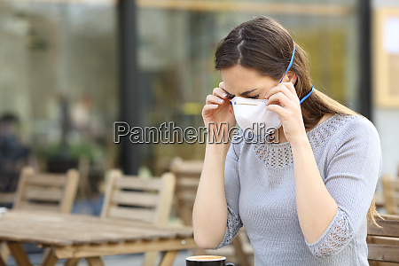 woman putting on protective mask at