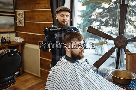 barbier mit kamm und haartrockner macht