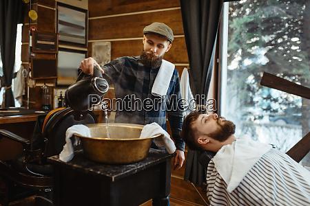 barbier traenkt das handtuch bart schneiden