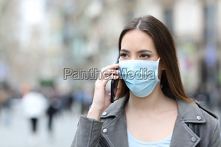 woman with mask talking on the