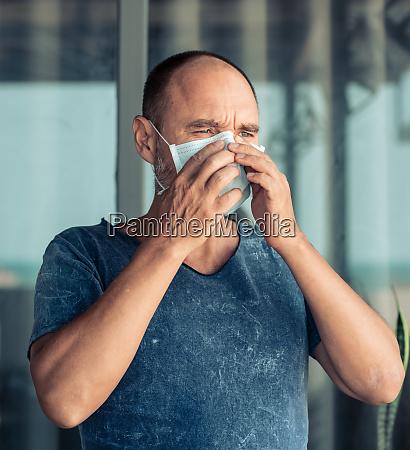 mann traegt gesichts einweg maske virenschutz