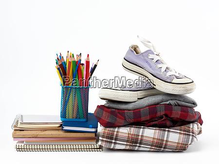 stapel gefalteter kleidung sportsneaker briefpapier auf