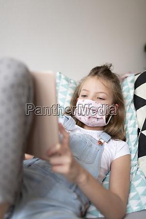 junges maedchen mit rosa schutzmaske zu