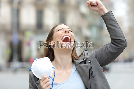 excited woman celebrating holding mask on