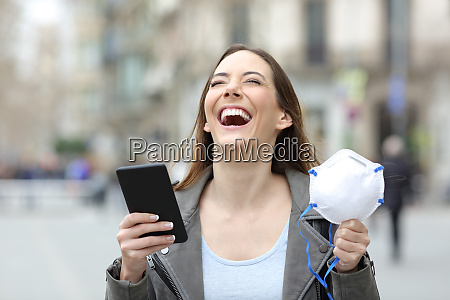 excited woman holding phone and mask