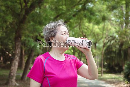 asiatische seniorin trinkwasser nach dem training