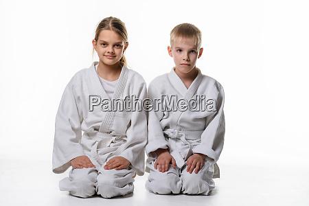zwei judo schueler sitzen auf den