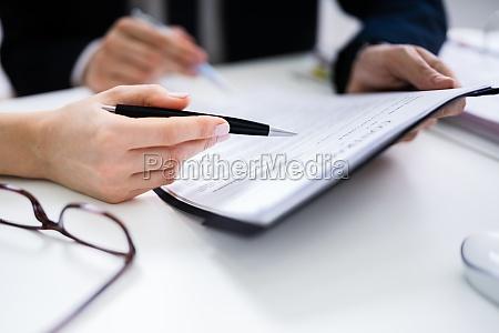 zwei geschaeftsleute analysieren dokument