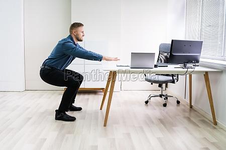 laechelnder junger geschaeftsmann bei sit ups