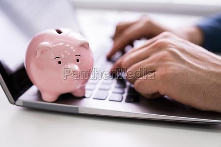 rosa piggy bank auf laptop