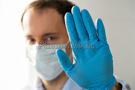 man making coronavirus pandemic stop gesture