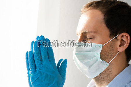 man praying during coronavirus pandemic