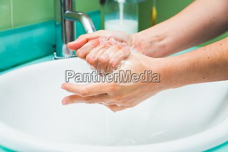 frau waschen haende unter dem wasserhahn
