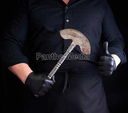 mann in schwarzer kleidung latexhandschuhe haelt