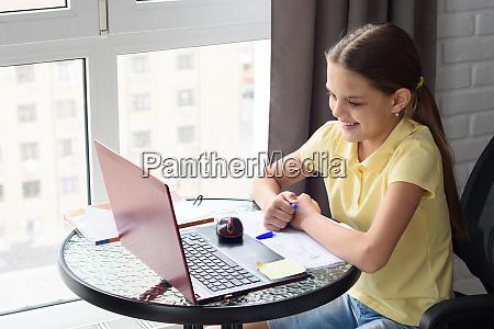 maedchen schaut freudig auf den laptop