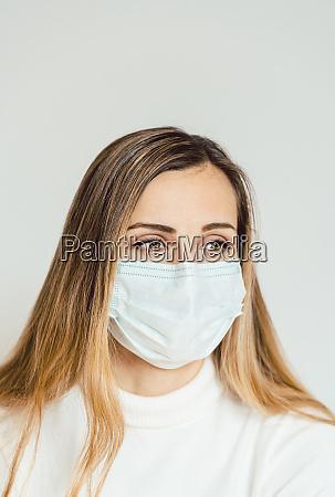 AEngstliche frau mit gesichtsmaske besorgt ueber