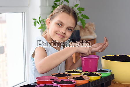 girl plants seeds in pots at