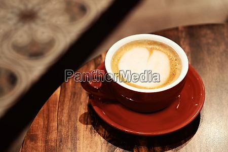 cappuccino tasse auf dem braunen holztisch