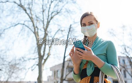 frau mit ihrem handy traegt maske