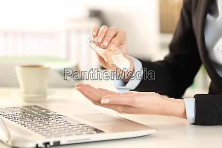 geschaeftsfrau putzt haende mit desinfektionsmittel im