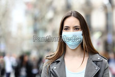 ernste frau mit maske die auf