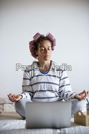 frau mit lockenwicklern meditieren auf dem