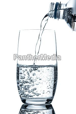 flasche mineralwasser giesst in glas im