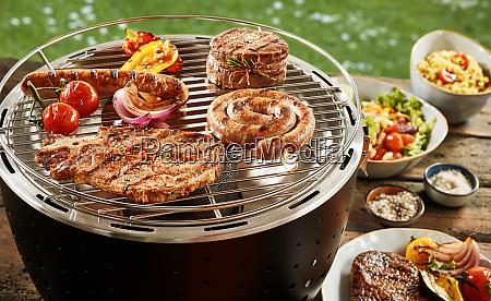 fruehlingsgrill mit verschiedenen fleisch und salaten